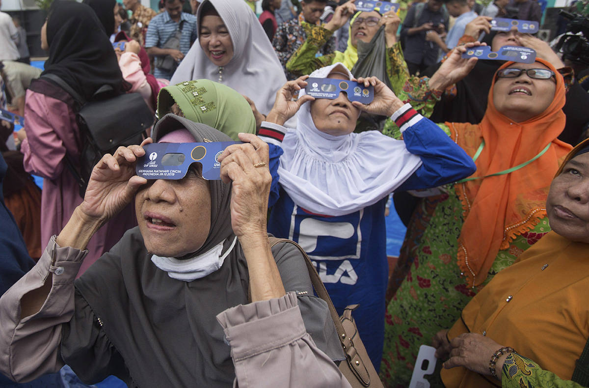 "Muslim women watch a solar eclipse through special glasses at the campus of the Faculty of Astronomy of Muhammadiah University of North Sumatra (UMSU) in Medan, Indonesia, Thursday, Dec. 26, 2019. People along a swath of southern Asia gazed at the sky in marvel on Thursday at a ""ring of fire"" solar eclipse. (AP Photo/Binsar Bakkara)"