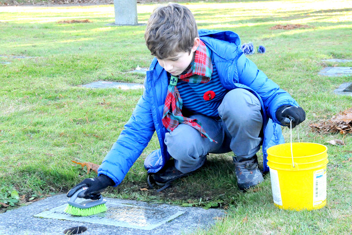 Nolan Facer, 11, a Langley Scout Troop member was at the Fort Langley cemetery in November, volunteering his time to clean headstones of fallen soldiers for the Remembrance Day ceremony. (Ryan Uytdewilligen/Langley Advance Times)