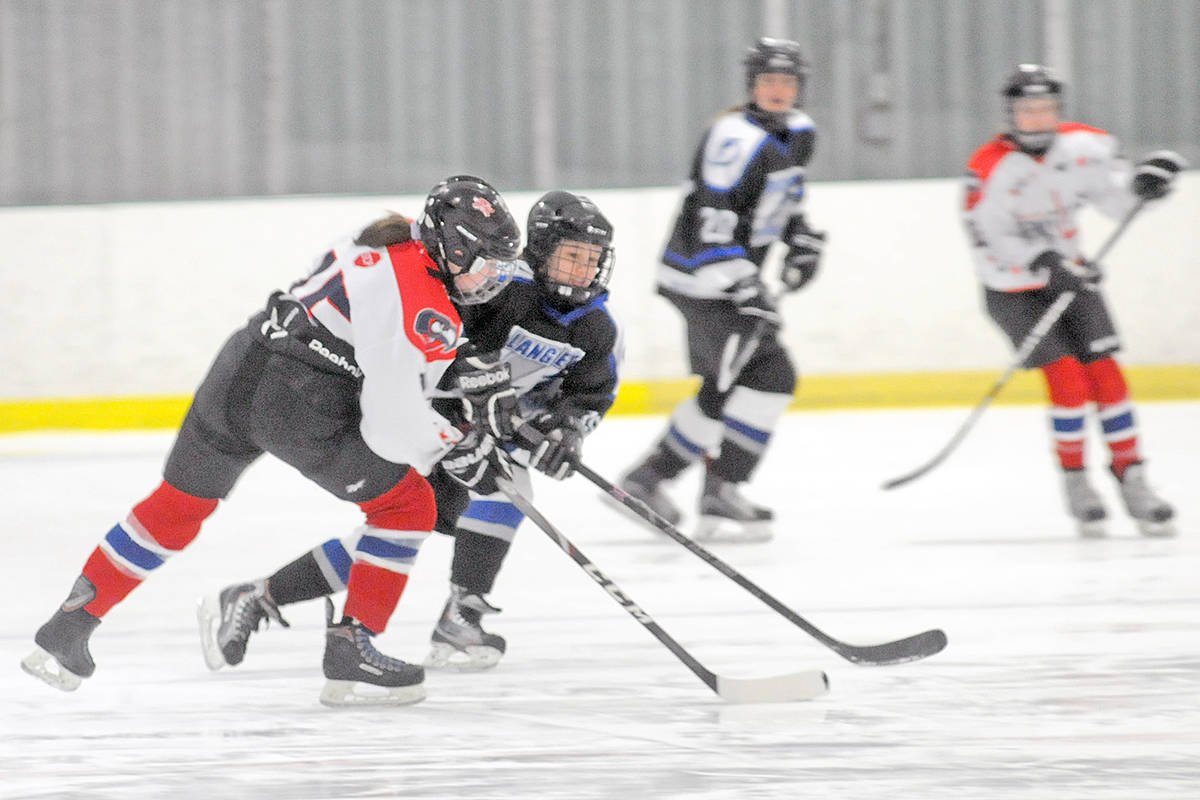 A Langley Lightning player tangled with a Cowichan rival Saturday (Dec. 28) at the start of the Angels On Ice tournament at the Langley Sportsplex. Langley won 3-1. Dan Ferguson/Langley Advance Times)