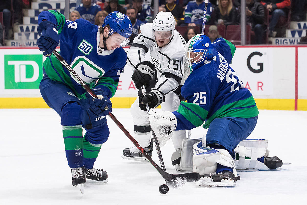 Los Angeles Kings' Austin Wagner (51) and Vancouver Canucks' Quinn Hughes (43) reach for the puck after Vancouver goalie Jacob Markstrom (25), of Sweden, made the save during first period NHL hockey action in Vancouver, Saturday, Dec. 28, 2019. THE CANADIAN PRESS/Darryl Dyck