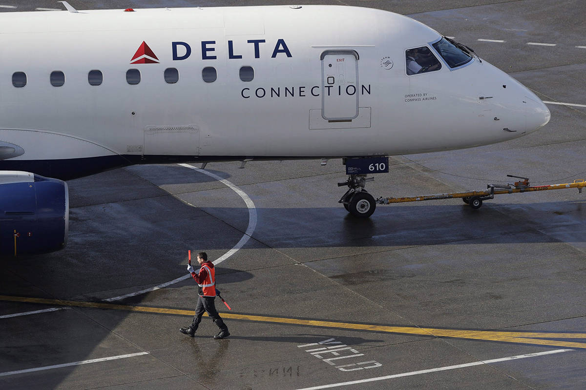 In this Feb. 5, 2019, file photo a ramp worker guides a Delta Air Lines plane at Seattle-Tacoma International Airport in Seattle. A 10-year-old girl from British Columbia has died after suffering a medical emergency aboard a flight in the United States.THE CANADIAN PRESS/AP/Ted S. Warren, File