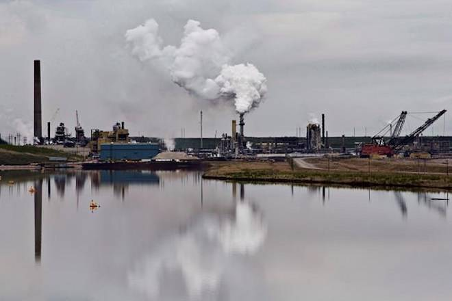 The Syncrude oil sands extraction facility is reflected in a tailings pond near the city of Fort McMurray, Alta., on June 1, 2014. THE CANADIAN PRESS/Jason Franson