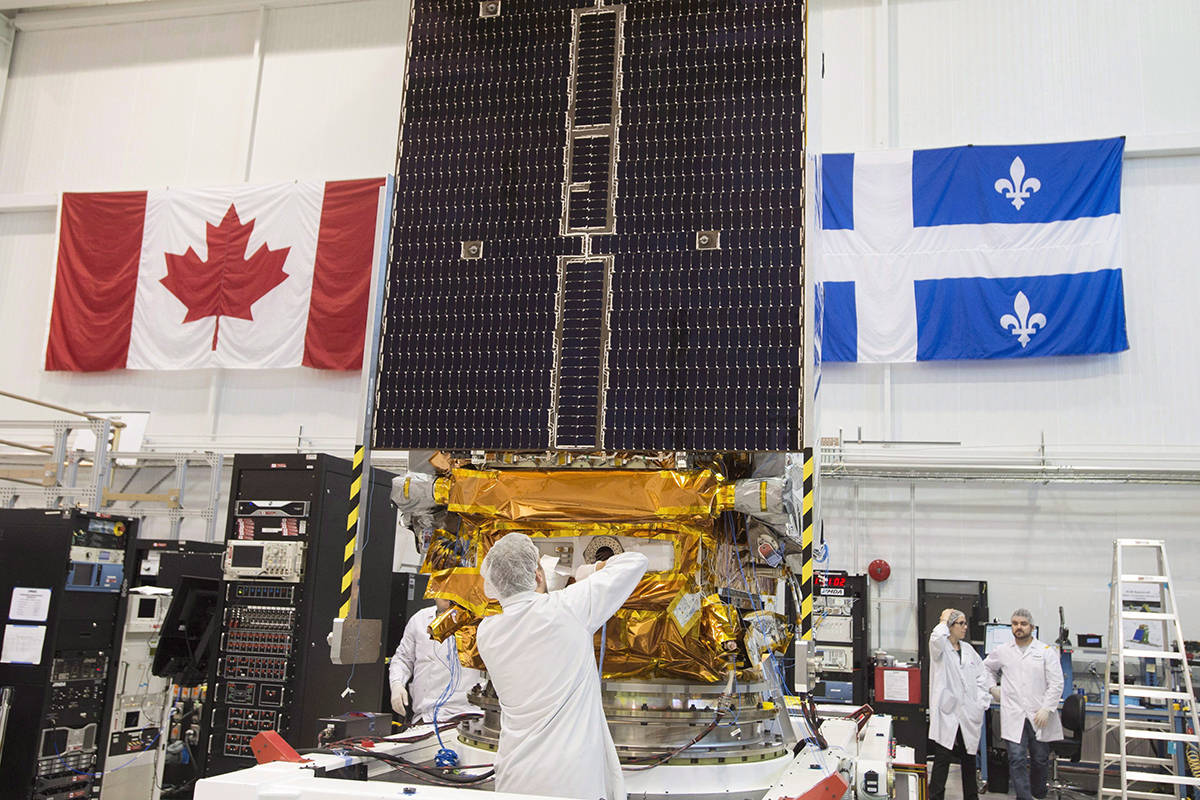 Technicians put the final touches on the second of three Radarsat Constellation Mission satellites at the MDA facility on June 21, 2018 in Montreal. A Toronto-based investment firm has signed a $1-billion deal to buy the Canadian space technology company behind Radarsat Earth-observation satellites and the Canadarm robotic mechanisms on the International Space Station. THE CANADIAN PRESS/Ryan Remiorz