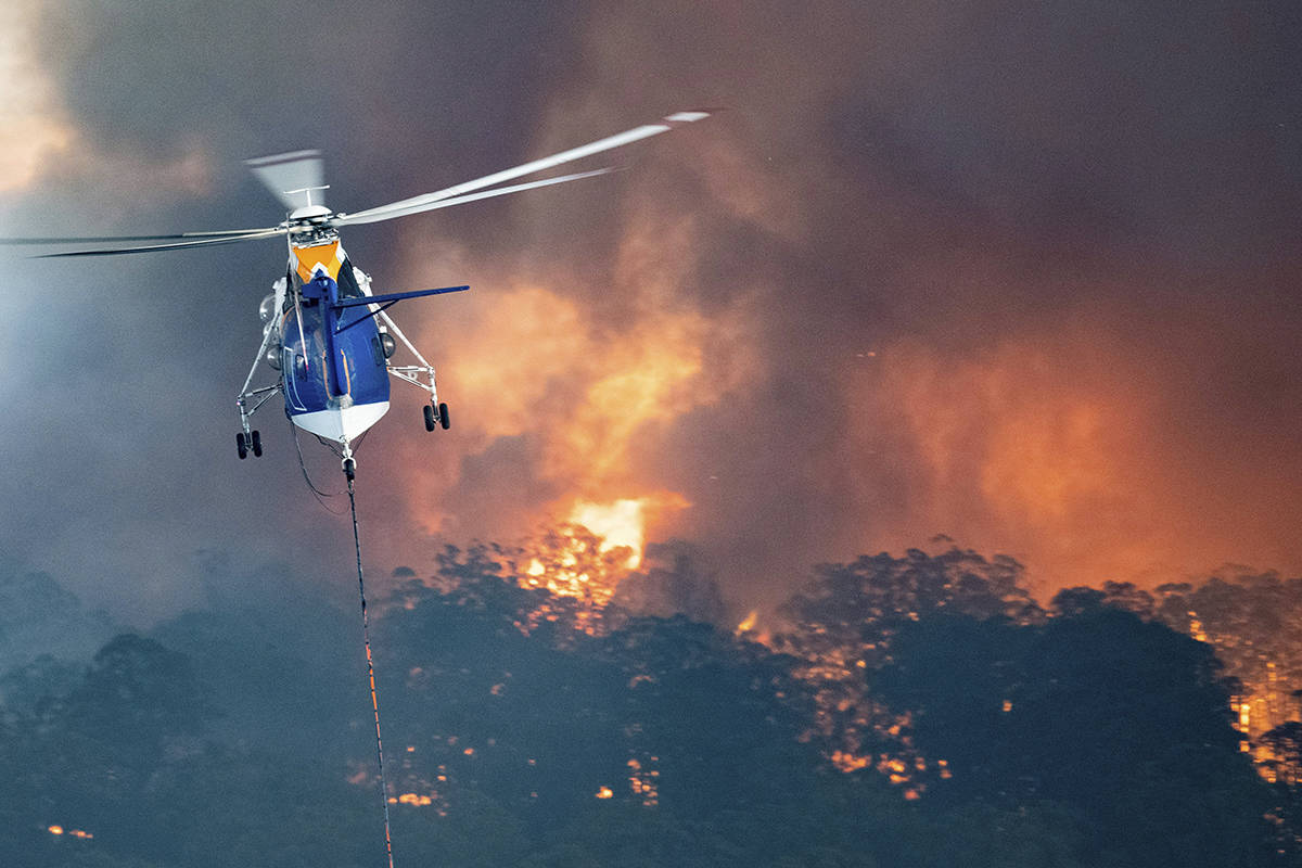 In this Monday, Dec. 30, 2019 photo provided by State Government of Victoria, a helicopter tackles a wildfire in East Gippsland, Victoria state, Australia. Wildfires burning across Australia's two most-populous states trapped residents of a seaside town in apocalyptic conditions Tuesday, Dec. 31, and were feared to have destroyed many properties and caused fatalities. (State Government of Victoria via AP)