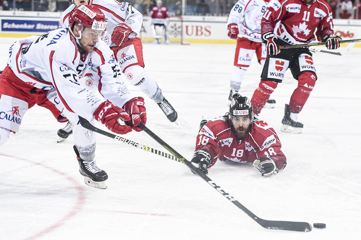 Trinec's Marian Adamek, left, against Team Canada's Mathew Maione during the final game between Team Canada and HC Ocelari Trinec at the 93th Spengler Cup ice hockey tournament in Davos, Switzerland, Tuesday, Dec. 31, 2019. (Melanie Duchene)/Keystone via AP)
