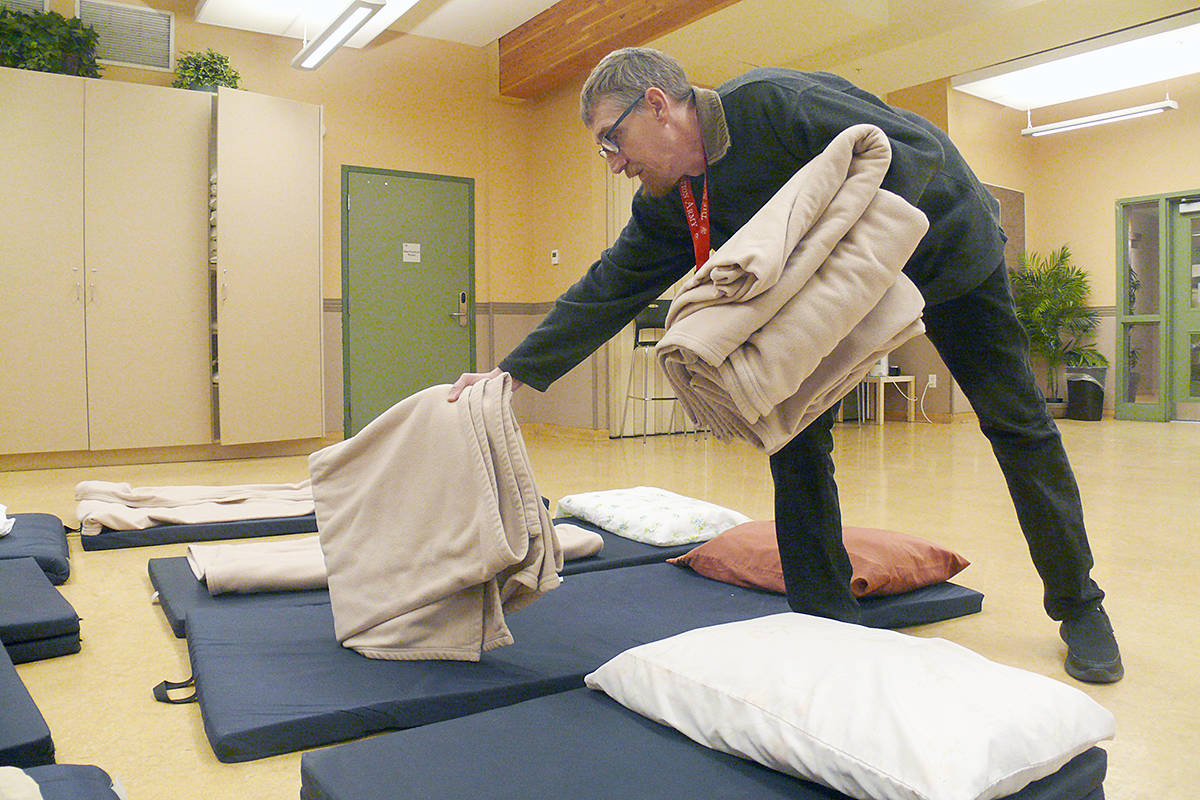 Gateway of Hope support worker Darren Skahl set out blankets and sleeping mats at the Langley shelter. A weather warning has been issues because of the damp conditions. (Dan Ferguson/Langley Advance Times)