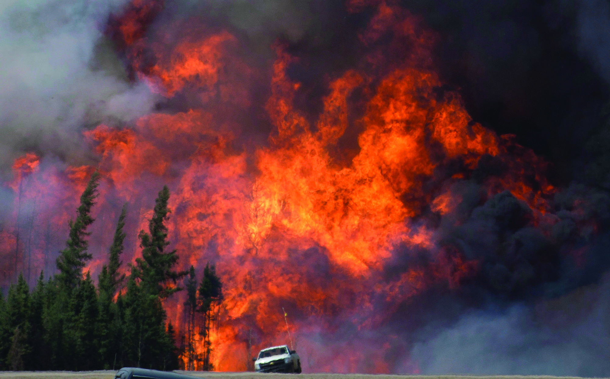 A giant fireball is seen as a wild fire rips through the forest 16 km south of Fort McMurray, Alberta on highway 63 on May 7, 2016. THE CANADIAN PRESS/Jonathan Hayward