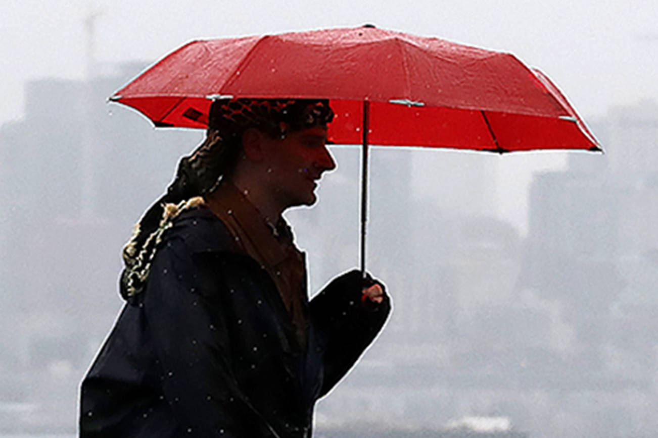 A pedestrian makes his way along a waterfront as downtown Seattle is partially hidden in a steady rain beyond Monday, Nov. 18, 2019. The rain and gray skies in the area are expected to give way to some sun and clouds over the next few days. (AP Photo/Elaine Thompson)                                A pedestrian makes his way along a waterfrontin a steady rain beyond Monday, Nov. 18, 2019. (AP Photo/Elaine Thompson)