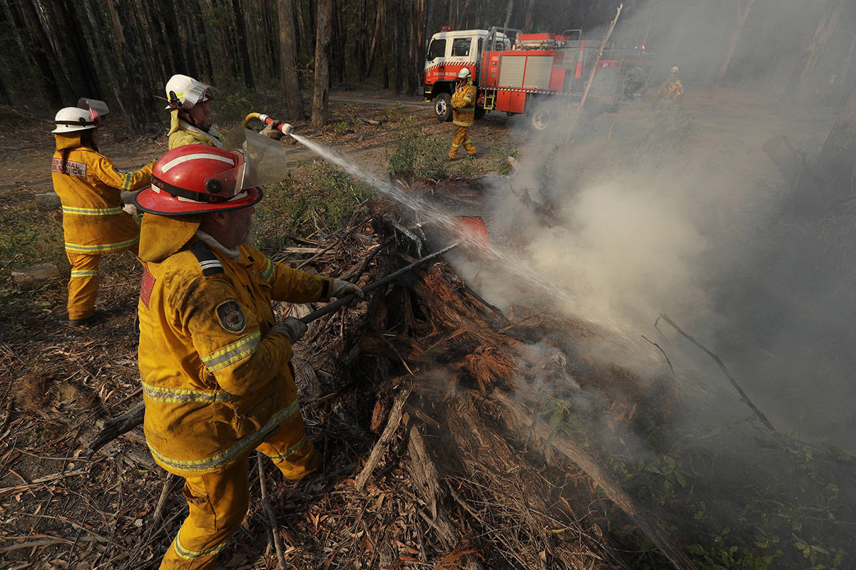 Firefighters battle a fire near Bendalong, Australia, Friday, Jan. 3, 2020. Navy ships plucked hundreds of people from beaches and tens of thousands were urged to flee before hot, windy weather worsens Australia's devastating wildfires. (AP Photo/Rick Rycroft)