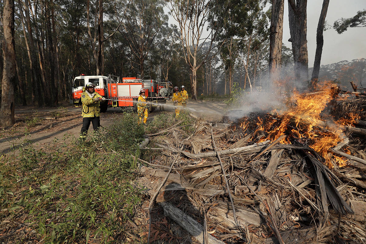 Firefighters battles a fire near Bendalong, Australia, Friday, Jan. 3, 2020. Navy ships plucked hundreds of people from beaches and tens of thousands were urged to flee before hot, windy weather worsens Australia's devastating wildfires. (AP Photo/Rick Rycroft)