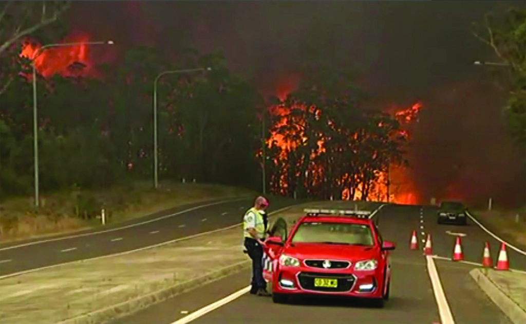 In this image made from video, officials block the Princes Highway as wildfires approach in South Coast, New South Wales Australia, Tuesday, Dec. 31, 2019. Wildfires burning across Australia's two most-populous states have trapped residents of a seaside town in apocalyptic conditions, destroyed many properties and caused fatalities. (Australian Broadcasting Corporation, Channel 9, Channel 7 via AP)