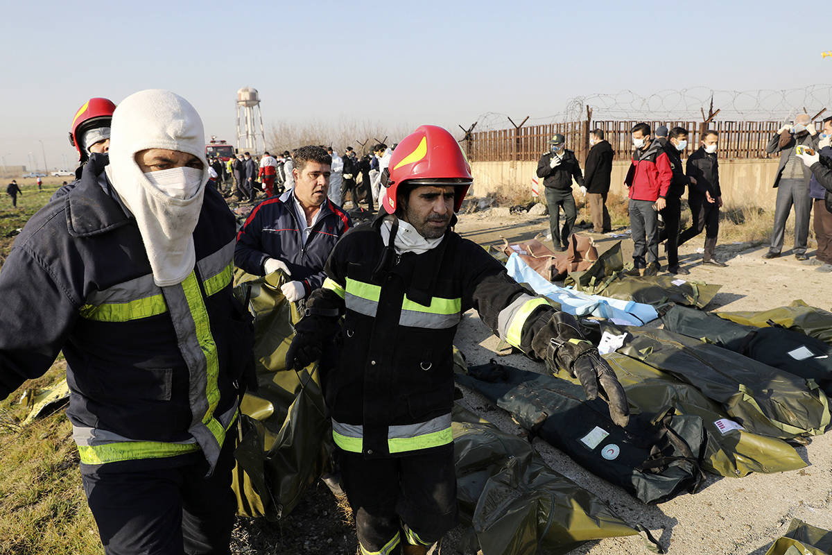Rescue workers carry the body of a victim of an Ukrainian plane crash in Shahedshahr, southwest of the capital Tehran, Iran, Wednesday, Jan. 8, 2020. A Ukrainian airplane carrying 176 people crashed on Wednesday shortly after takeoff from Tehran's main airport, killing all onboard. (AP Photo/Ebrahim Noroozi)