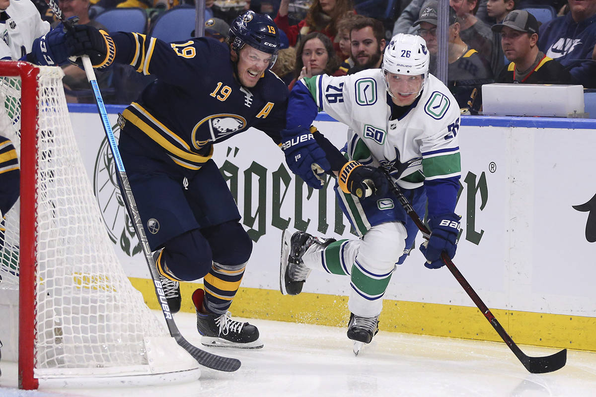 Buffalo Sabres defenceman Jake McCabe (19) and Vancouver Canucks forward Antoine Roussel (26) battle behind the net during the second period of an NHL hockey game Saturday, Jan. 11, 2020, in Buffalo, N.Y. (AP Photo/Jeffrey T. Barnes)