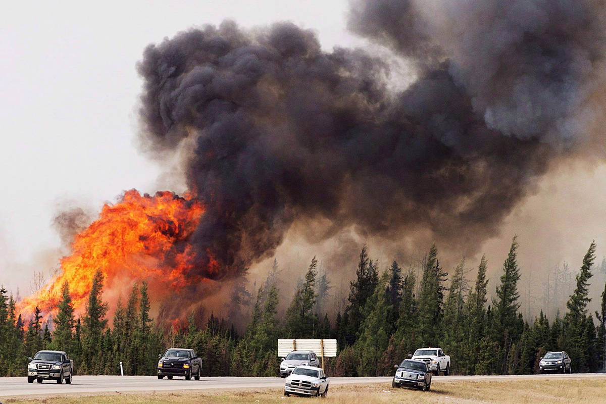 A convoy of evacuees from Fort McMurray, Alberta drive past wildfires that are still burning out of control as they leave the city Saturday, May 7, 2016. The increasing frequency of wildfires in Canada's boreal forest may be permanently changing one of the largest intact ecosystems left on Earth, new research suggests.THE CANADIAN PRESS/Ryan Remiorz