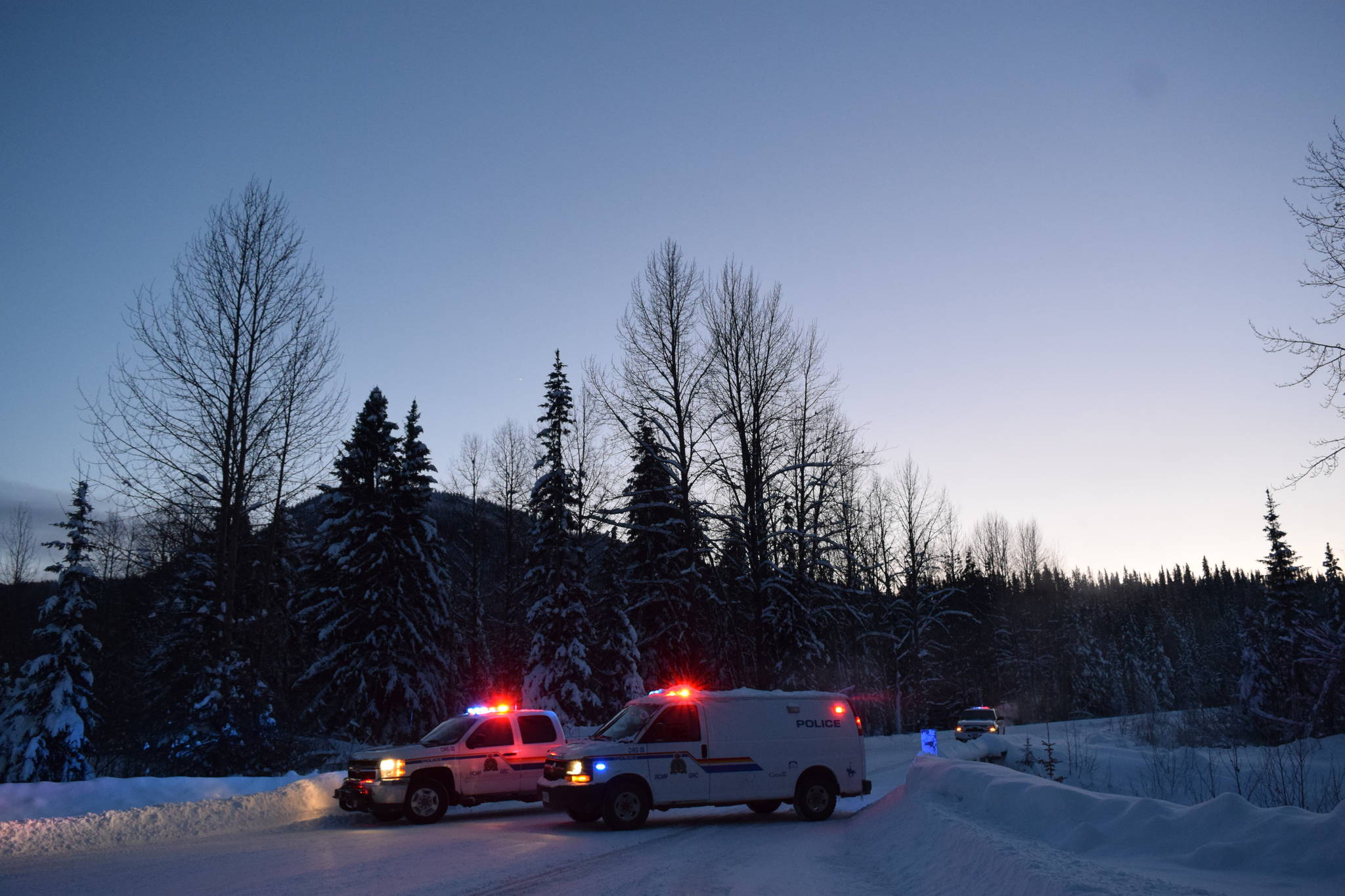 RCMP vehicles pictured at the 27-kilometre mark of Morice West Forest Service Road. The RCMP has said they have set up the check point to assure safety and mitigate concerns surrounding a number of hazardous items found in close proximity to a number of felled logs further down the road. (Trevor Hewitt photo)
