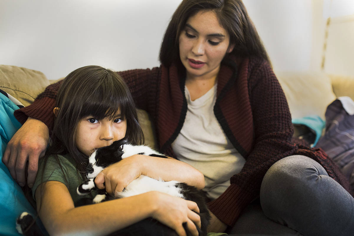 Mackenzie Smith holds Luna close as mom Ashley Smith sits next to them. Luna had been missing since Oct. 8, 2019. She was recently reunited with the family after being missing for about three months in Campbell River, B.C. Photo by Marissa Tiel/ Campbell River Mirror