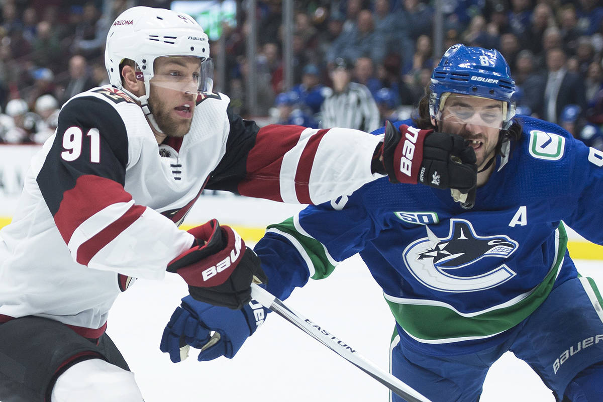 Arizona Coyotes left wing Taylor Hall (91) fights for control of the puck with Vancouver Canucks defenceman Christopher Tanev (8) during first period NHL action in Vancouver, Thursday, January 16, 2020. THE CANADIAN PRESS/Jonathan Hayward