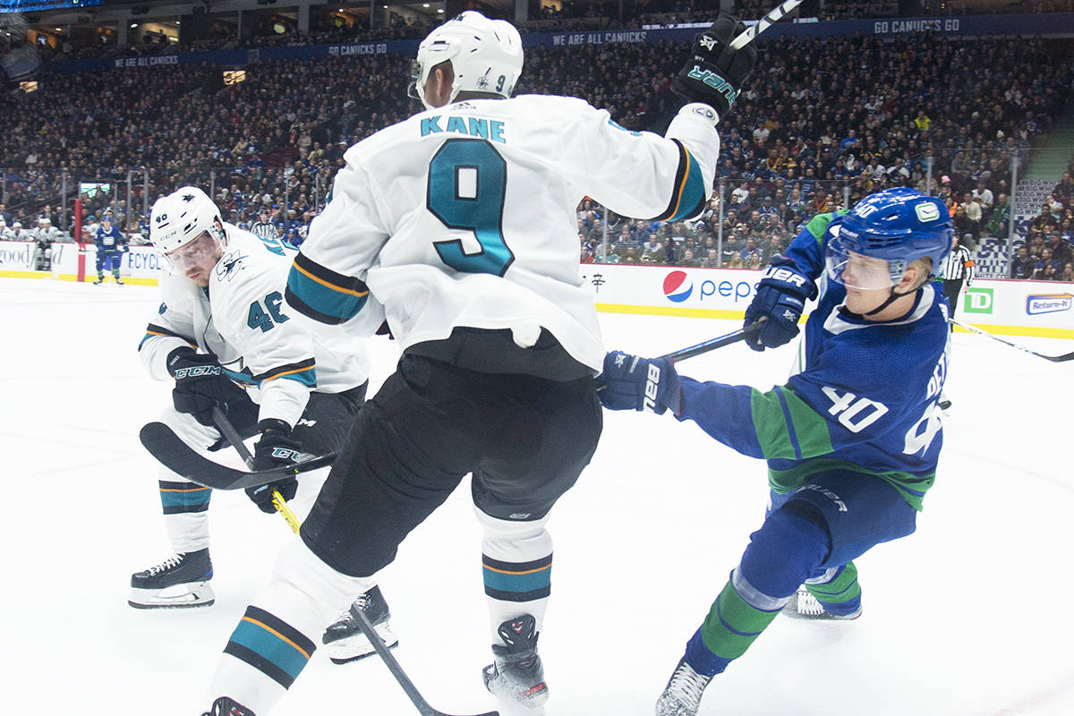 Vancouver Canucks centre Elias Pettersson (40) fights for control of the puck with San Jose Sharks left wing Evander Kane (9) during first period NHL hockey action in Vancouver, Saturday, Jan. 18, 2020. THE CANADIAN PRESS/Jonathan Hayward