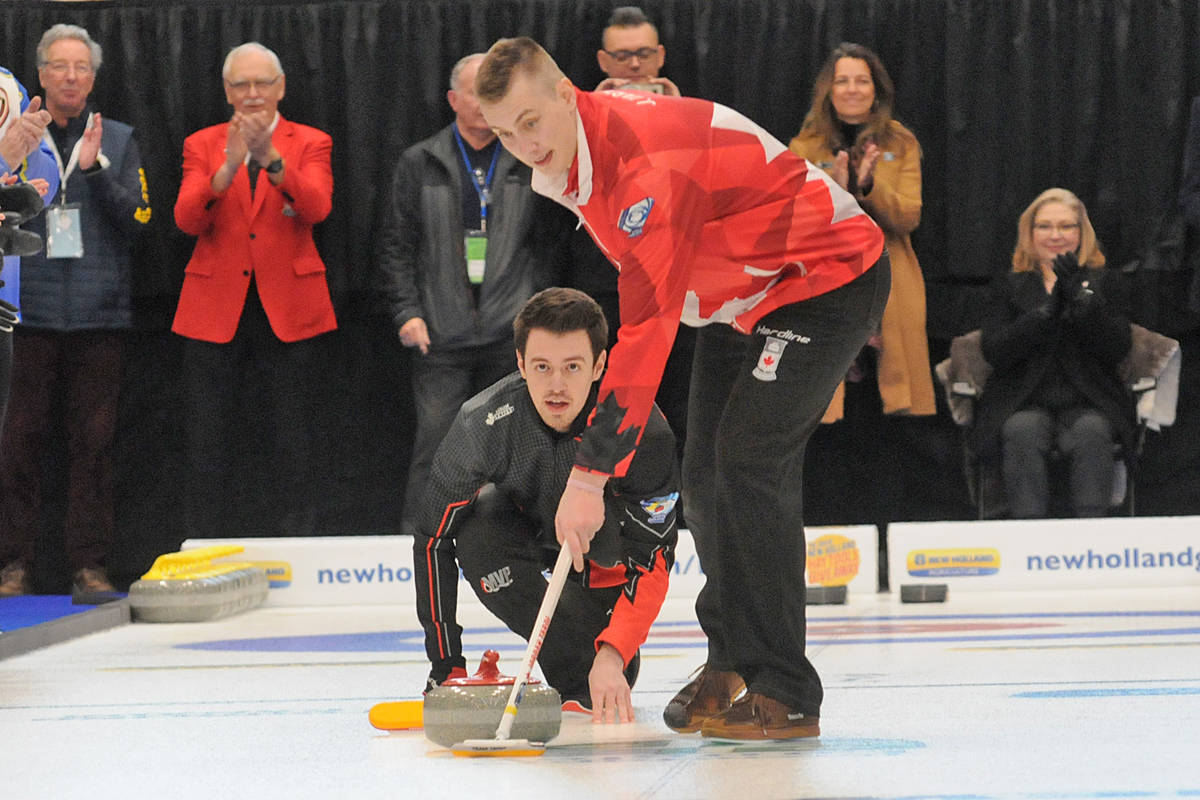Tyler Tardi threw the ceremonial opening rock at the opening ceremonies of the 2020 New Holland Canadian Junior Championships of curling at the George Preston rec centre on Saturday, with Jordan Tardi sweeping. (Dan Ferguson/Langley Advance Times)
