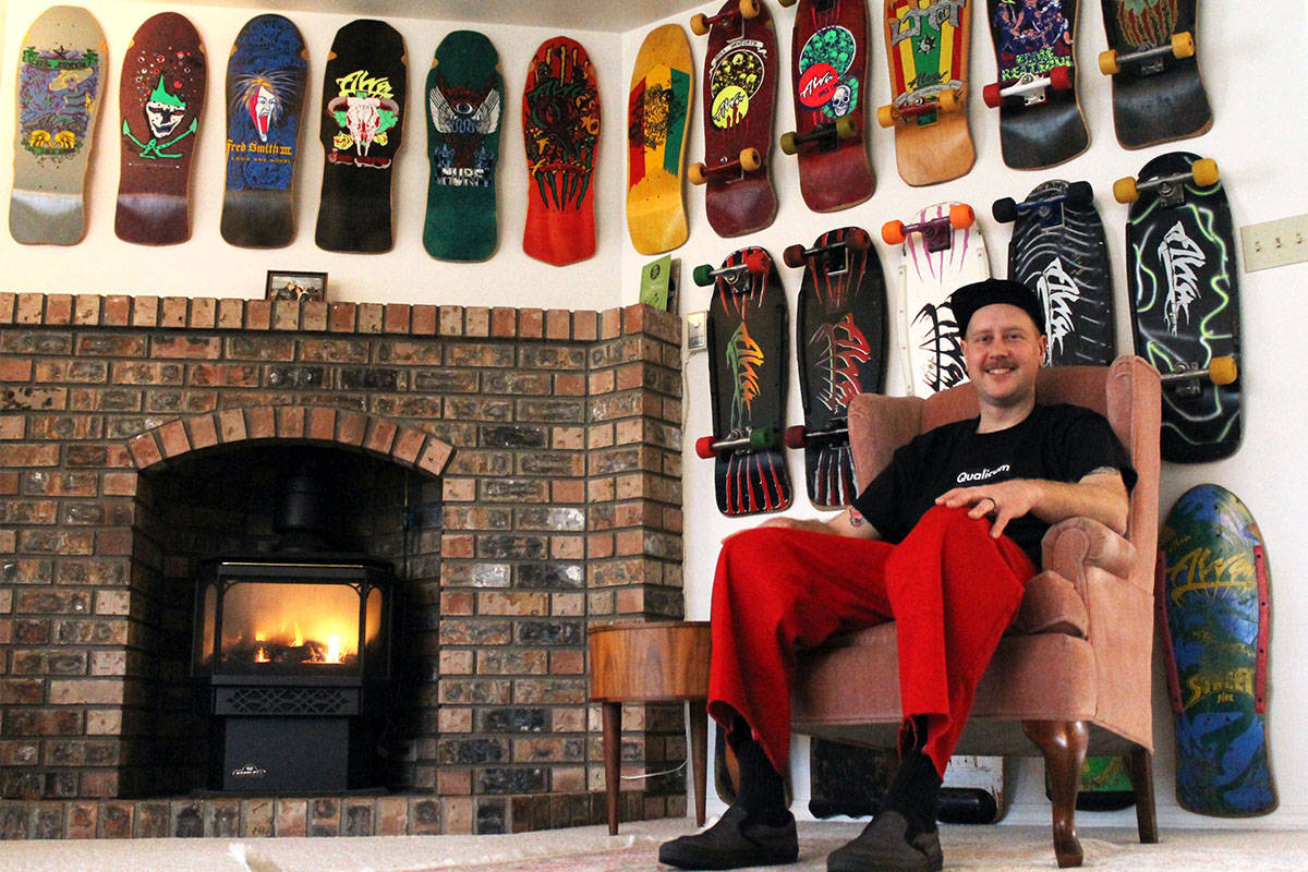 In Eric Pinto's Qualicum Beach home, the walls are lined with historic skateboards, many of them full setups of era-accurate components. Pictured behind Pinto is a collection of Alva Skates boards. (Emily Vance photo)