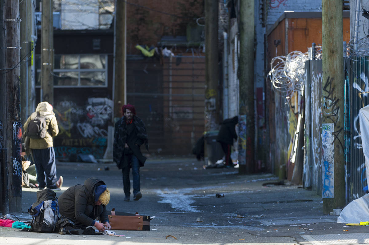 People are seen in an alleyway in Vancouver's Downtown Eastside, Wednesday, Feb. 6, 2019. British Columbia's chief coroner is to release statistics for illicit drug overdose deaths in 2018 on Thursday. THE CANADIAN PRESS/Jonathan Hayward