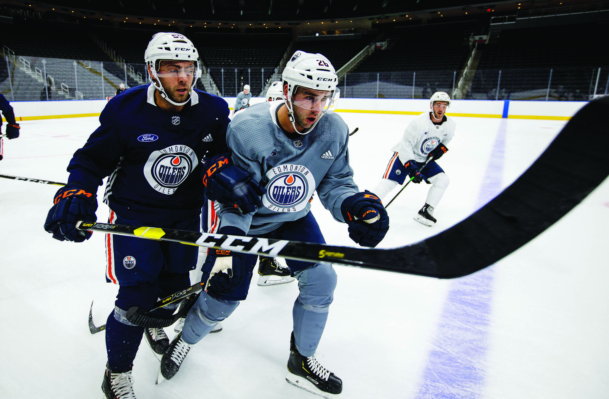 Edmonton Oilers Luke Esposito (55) and Brandon Manning (26), right, battle for the puck during training camp in Edmonton on Friday, Sept. 13, 2019. THE CANADIAN PRESS/Jason Franson