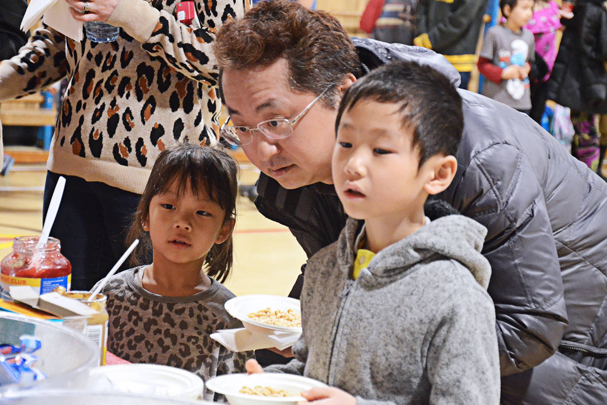 Dad Takashi Kagami and his children Takaharu, right, and Mayuki, left, were among those getting breakfast at Willoughby Elementary on Friday. (Matthew Claxton/Langley Advance Times)