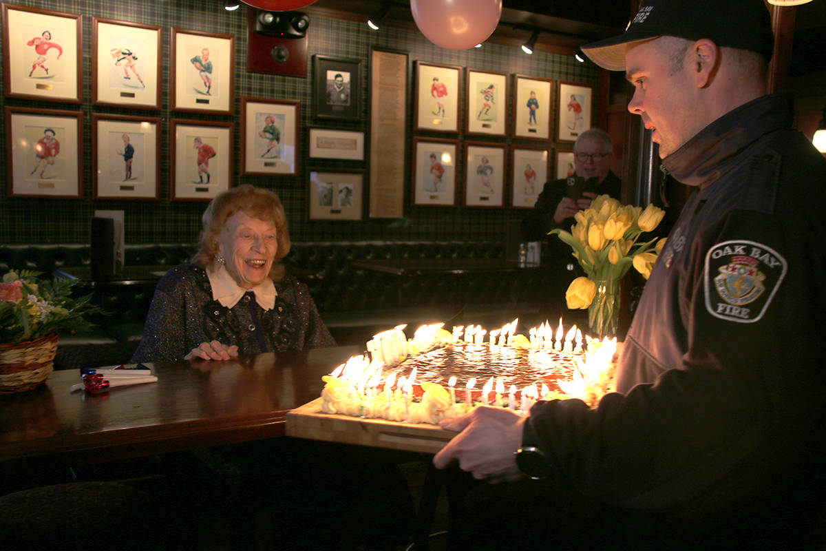 Constance Isherwood is presented a birthday cake with a 100 candles on top by Oak Bay fire fighter Jason Ahokas. (Kendra Crighton/News Staff)