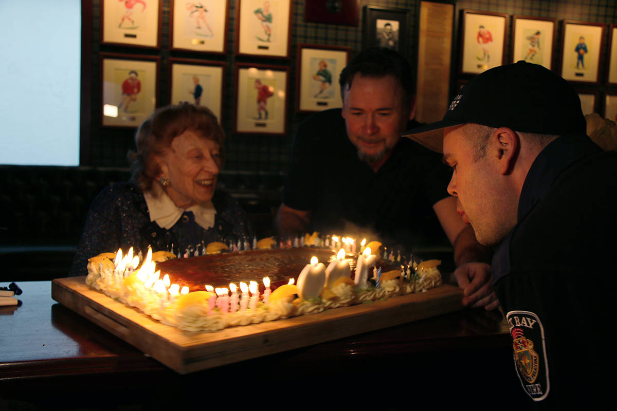 Oak Bay firefighter Jason Ahokas and son, George, help 100-year-old Constance Isherwood blow out all the candles on her birthday cake. (Kendra Crighton/News Staff)