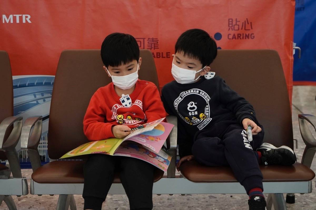 Passengers wear masks to prevent an outbreak of a new coronavirus in the high speed train station, in Hong Kong, on Jan. 22, 2020. (AP Photo/Kin Cheung)