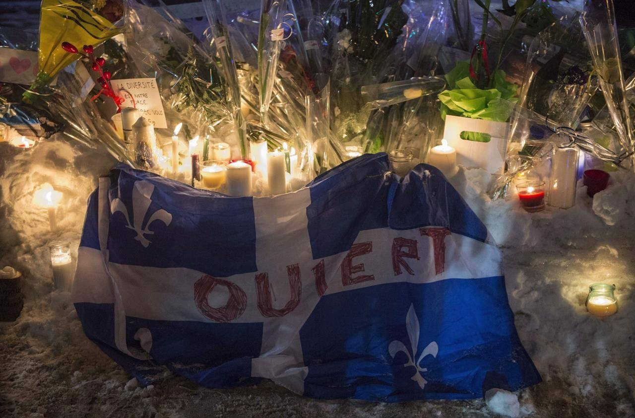 """A Quebec flag with the word """"Open"""" written on it is shown in remembrance of six victims of a shooting at mosque during a vigil in Quebec City on January 30, 2017. Events are being held Wednesday in Quebec City to mark the third anniversary of the deadly mosque shooting that claimed six lives. Organizers from the citizens group """"We remember January 29"""" said the Quebec Islamic Cultural Centre where the killings occurred will open its doors to the community this afternoon, with a dinner and speeches later at an area church. THE CANADIAN PRESS/Paul Chiasson"""