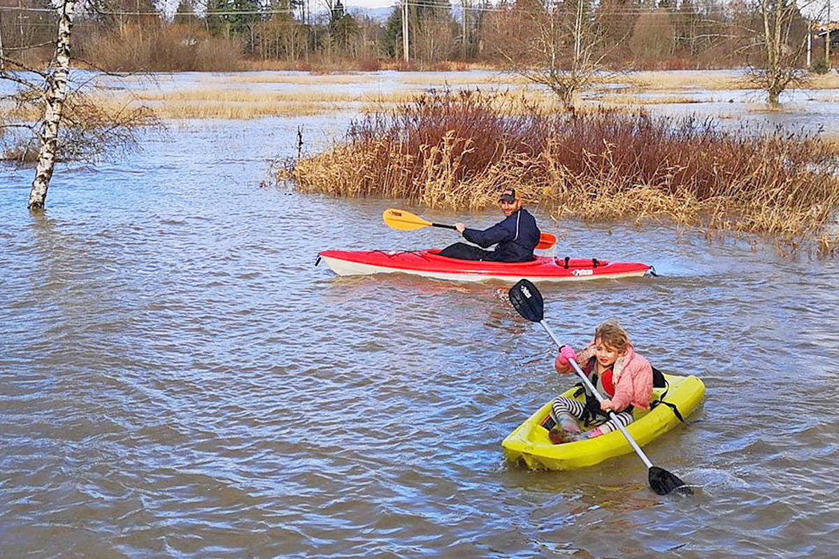 Langley City resident Joe Melissen and his five-year-old daughter Mae did some paddling in their back yard after heavy rain overnight raised the level of the Nicomekl River in the area of 197 Street and 51 Avenue on Saturday, Feb. 1. Their house was on higher ground above the flood plain, and not affected. (Bryan Grim/special to Langley Advance Times)