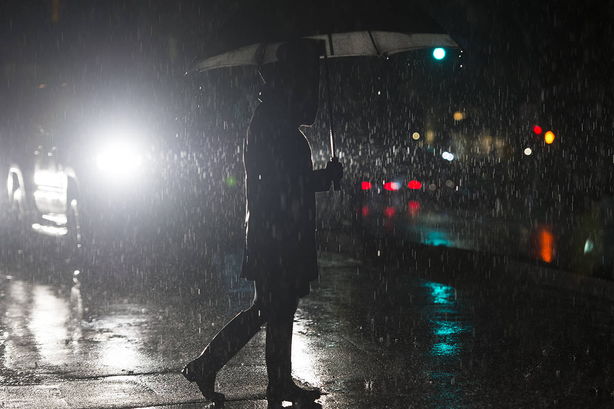 A pedestrian is seen crossing the street in North Vancouver B.C, Friday, January, 31, 2020. Another rain storm has hit the lower mainland with a expected rain fall of over 100mm in the last day of January. THE CANADIAN PRESS/Jonathan Hayward