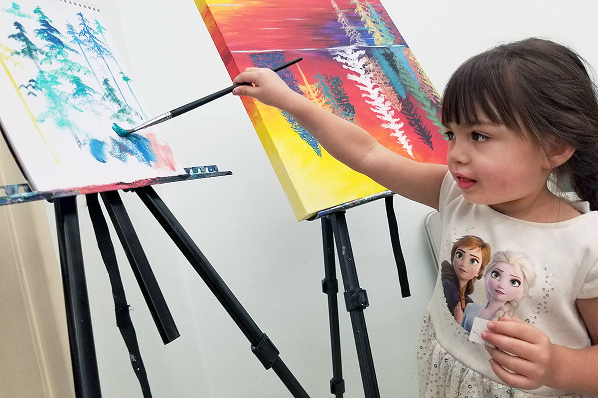 Lynnaea, 3, tried her hand at a collaborative painting project during the One Table community dinner at the Shepherd of the Valley church in Langley on Saturday, (Feb. 1). (Dan Ferguson/Langley Advance Times)
