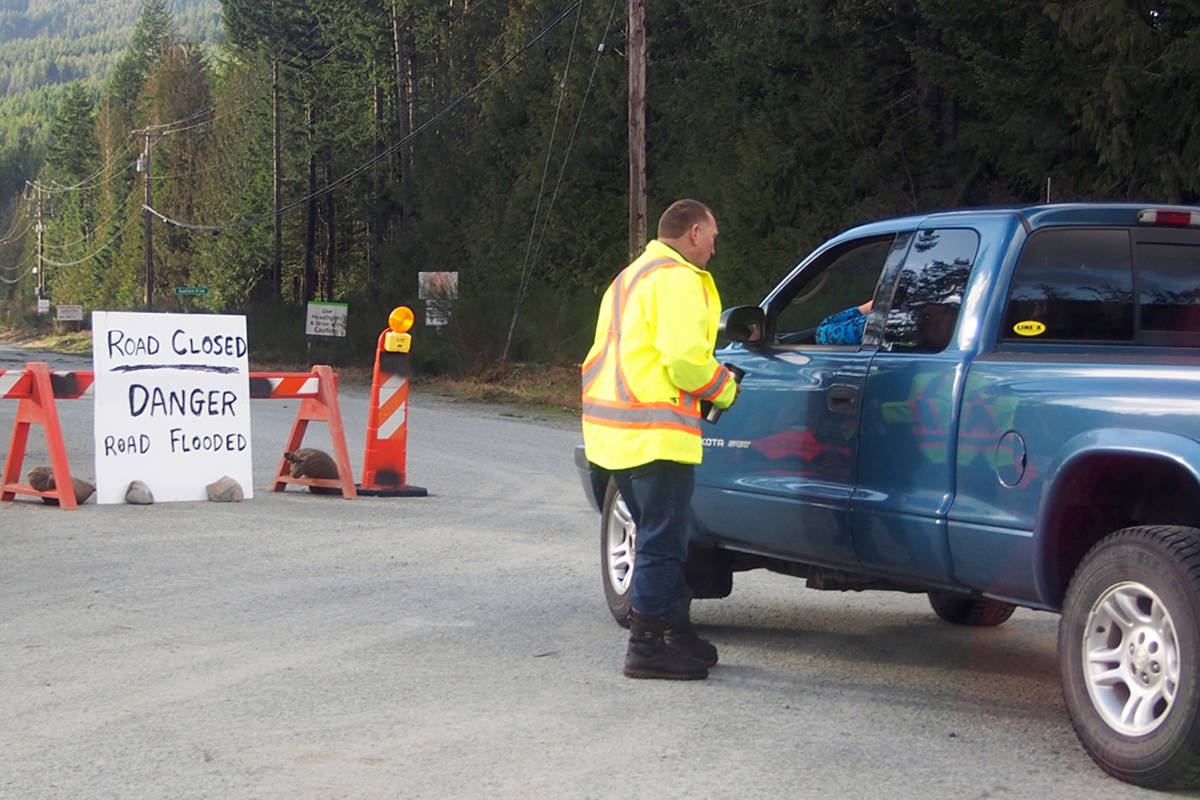 Tom Jarvis speaks with a driver at the start of Bamfield Main on Saturday, Feb. 1, 2020. Heavy rain from an 'atmospheric river' that hit the west coast of British Columbia on the weekend caused several washouts on the 88-kilometre road. (MIKE YOUDS/ Special to the News)