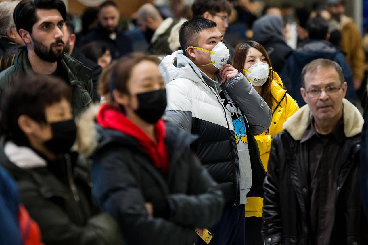 People wear masks as they wait for the arrivals at the International terminal at Toronto Pearson International Airport in Toronto on Saturday, January 25, 2020. Leaders of Toronto's Chinese community said the racist attitudes that led to widespread discrimination against Chinese Canadians during the SARS epidemic are threatening to resurface during the current outbreak of a new coronavirus.THE CANADIAN PRESS/Nathan Denette