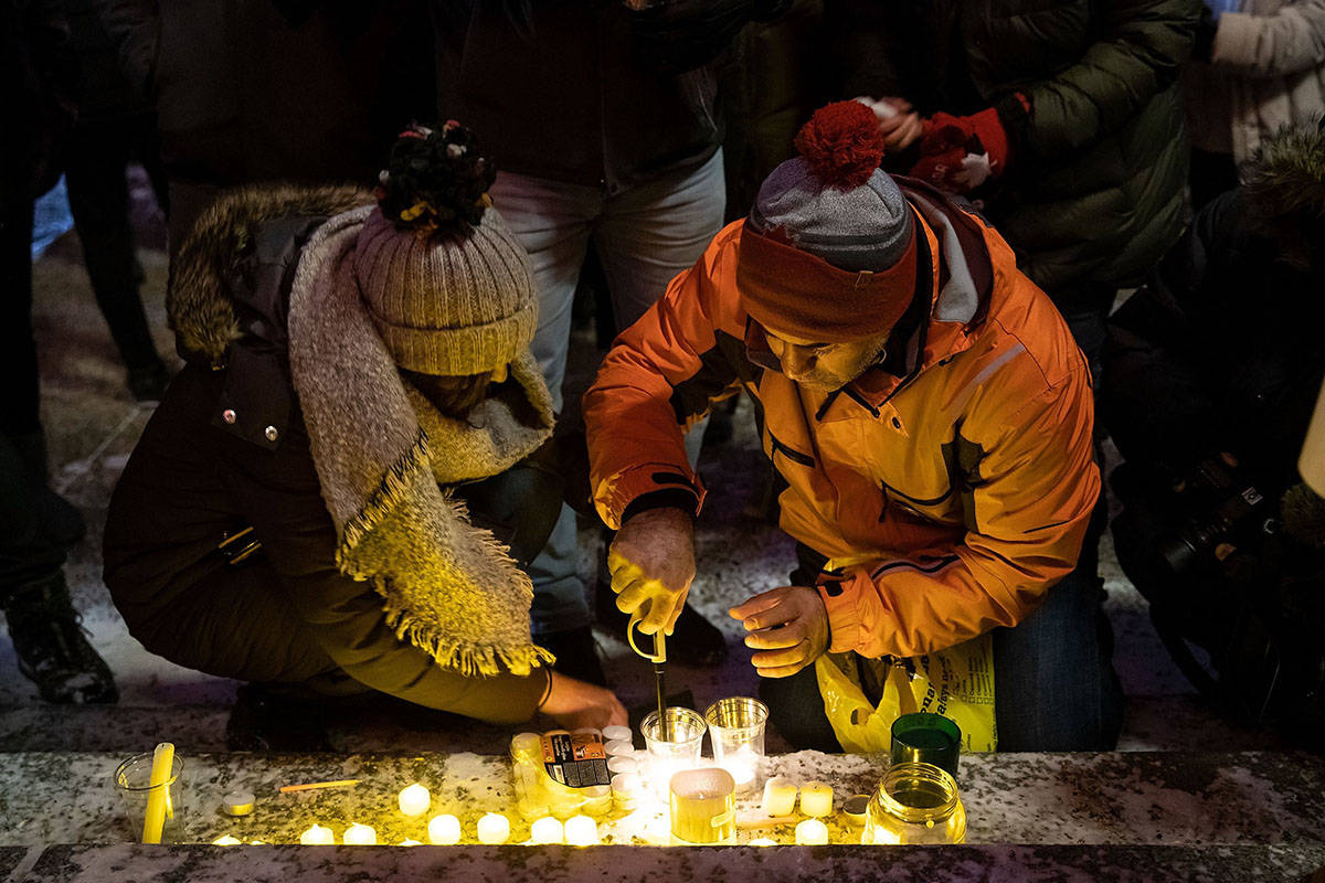 Mourners place candles and photographs during a vigil for those who were among the 176 people who were killed when Ukraine International Airlines Flight PS752 crashed after takeoff near Tehran, Iran, outside the Alberta Legislature Building in Edmonton on Wednesday, Jan. 8, 2020. THE CANADIAN PRESS/Codie McLachlan