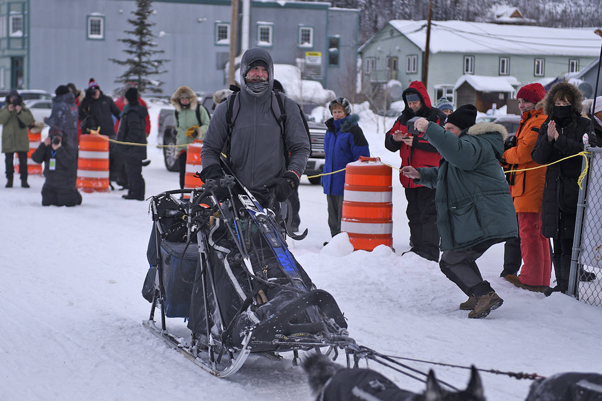 A man named Jason arrives at the Dawson checkpoint on Richie Beattie's sled after he found the team running alone near Moosehide on Feb. 7. (John Hopkins-Hill/Yukon News)