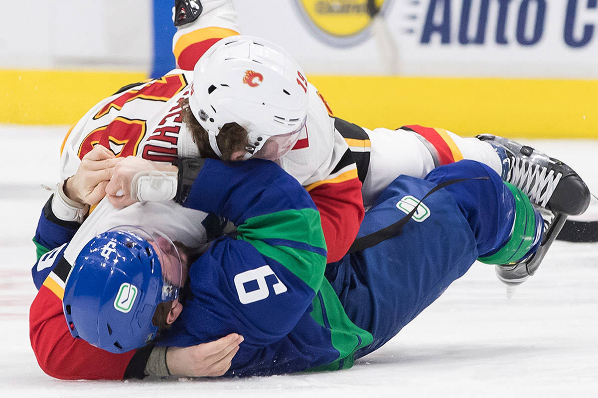 Calgary Flames' Matthew Tkachuk (19) and Vancouver Canucks' J.T. Miller (9) fight during the first period of an NHL hockey game in Vancouver, on Saturday February 8, 2020. THE CANADIAN PRESS/Darryl Dyck