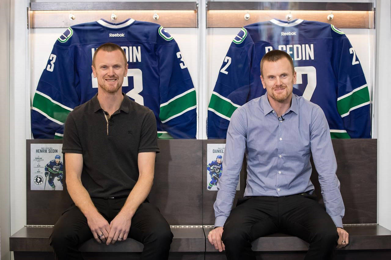 Former Vancouver Canucks' Henrik Sedin, left, and his twin brother Daniel Sedin, both of Sweden, pose for a photograph during a media availability ahead of a Wednesday ceremony where the NHL hockey team is scheduled to retire their numbers, in Vancouver, on Monday, February 10, 2020. THE CANADIAN PRESS/Darryl Dyck