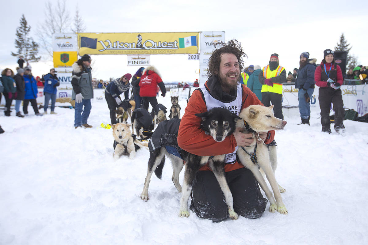 Brent Sass poses with his lead dogs after crossing the finish line in Whitehorse on Feb. 11 to win his third Yukon Quest. (Crystal Schick/Yukon News)