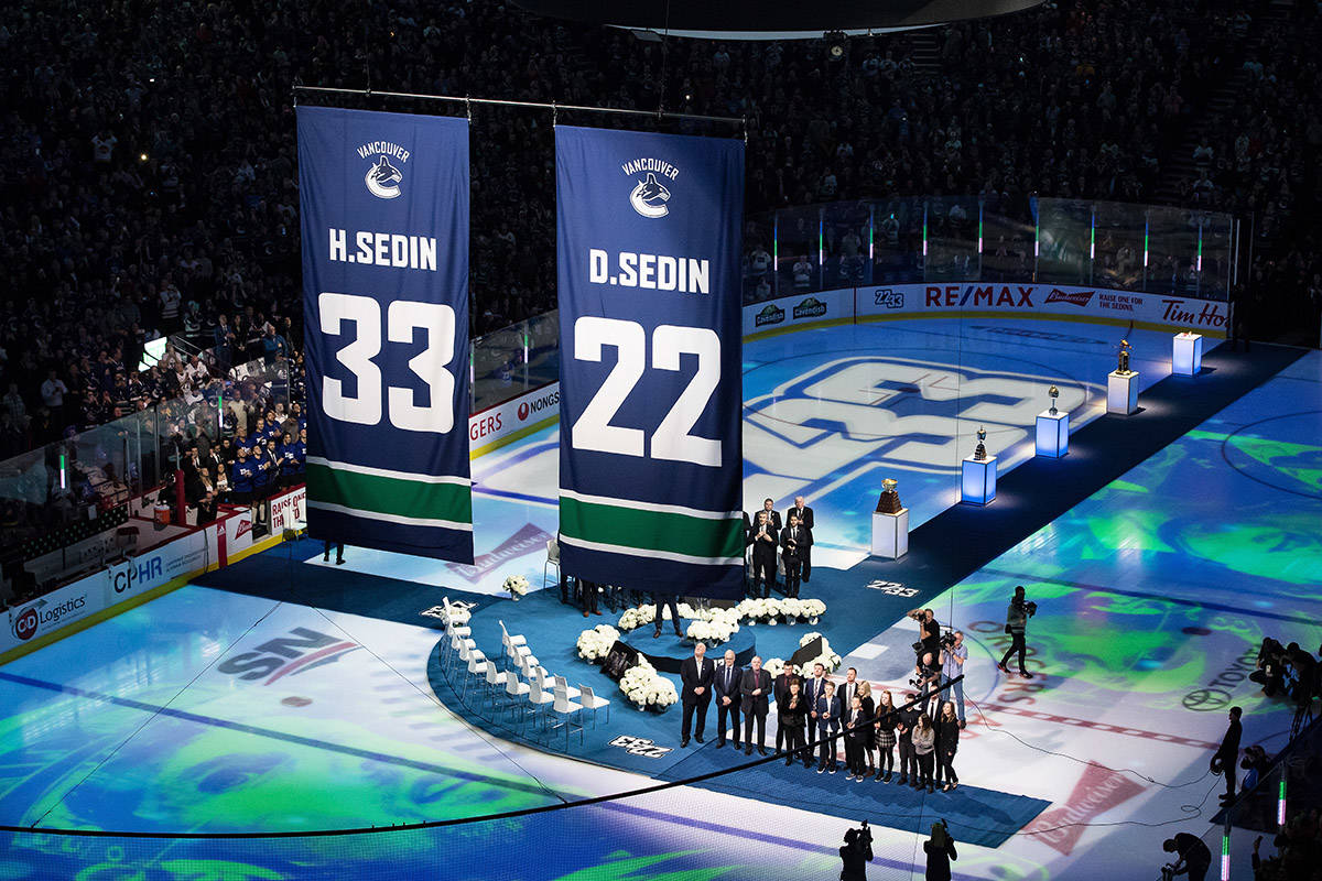 Former Vancouver Canucks players Henrik Sedin and his twin brother Daniel Sedin, both of Sweden, and their families watch as their numbers are raised to the rafters during a jersey retirement ceremony before an NHL hockey game in Vancouver, on Wednesday February 12, 2020. THE CANADIAN PRESS/Darryl Dyck