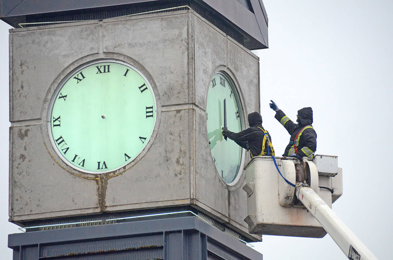 Workers replace the hands on the Five Corners clock tower. They were back up on Feb. 16, 2018 after being removed Jan. 17, 2018 for repair. Now the whole thing is up for repair and replacement from Feb. 15 to Feb. 17, 2020. (Paul Henderson/ The Progress)