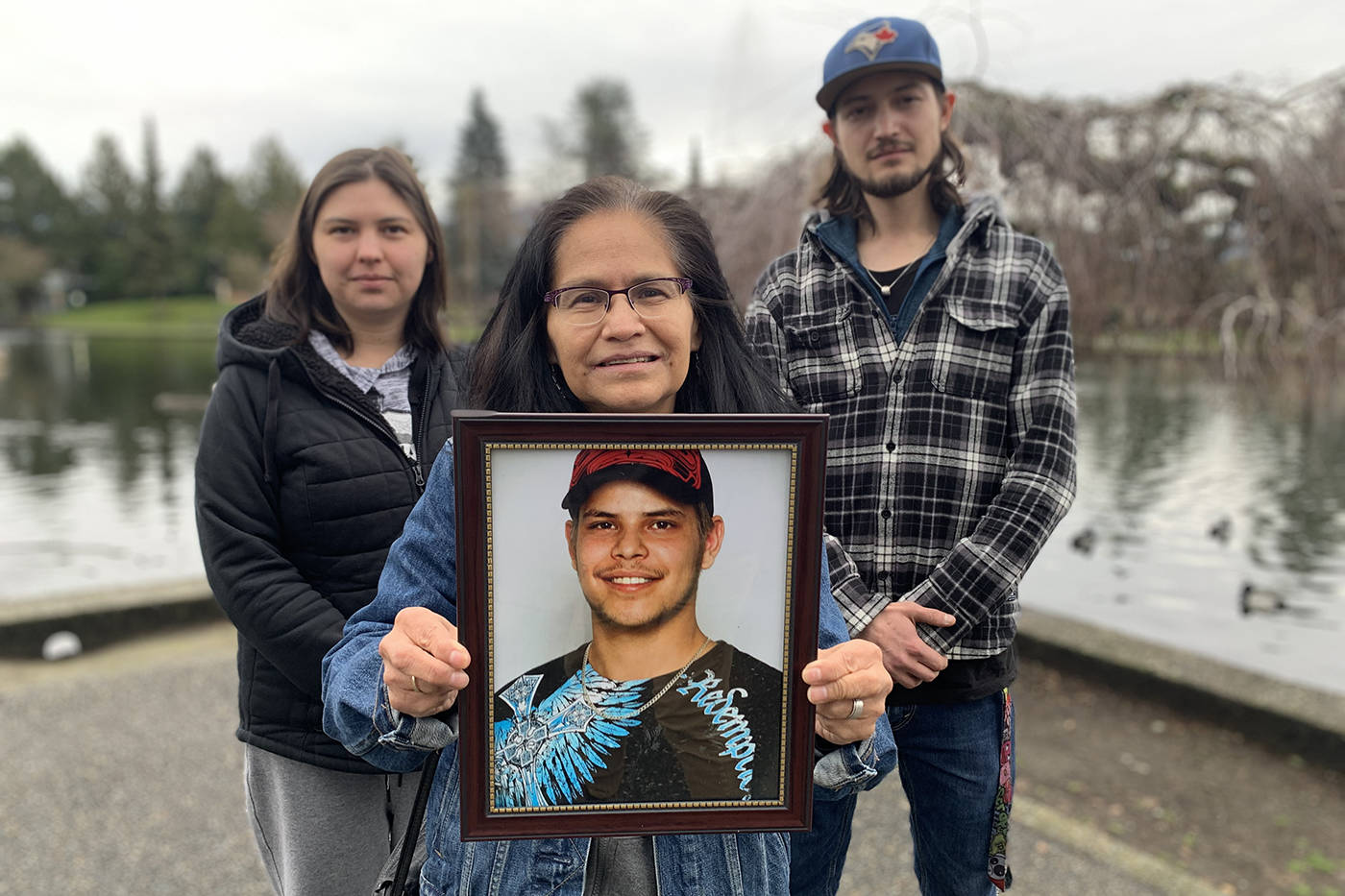 Flanked by her daughter Sarah and eldest son Jared, Maggie Smith holds a photograph of her son Tim Postma who died on the streets of Chilliwack on Jan. 22, 2020. (Paul Henderson/ The Progress)