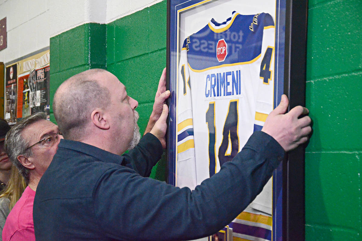 Carson Crimeni's father Aron (right) and his grandfather Darrel (left) hang Carson's jersey at the Langley Sportsplex where the late 14-year-old played. (Matthew Claxton/Langley Advance Times)
