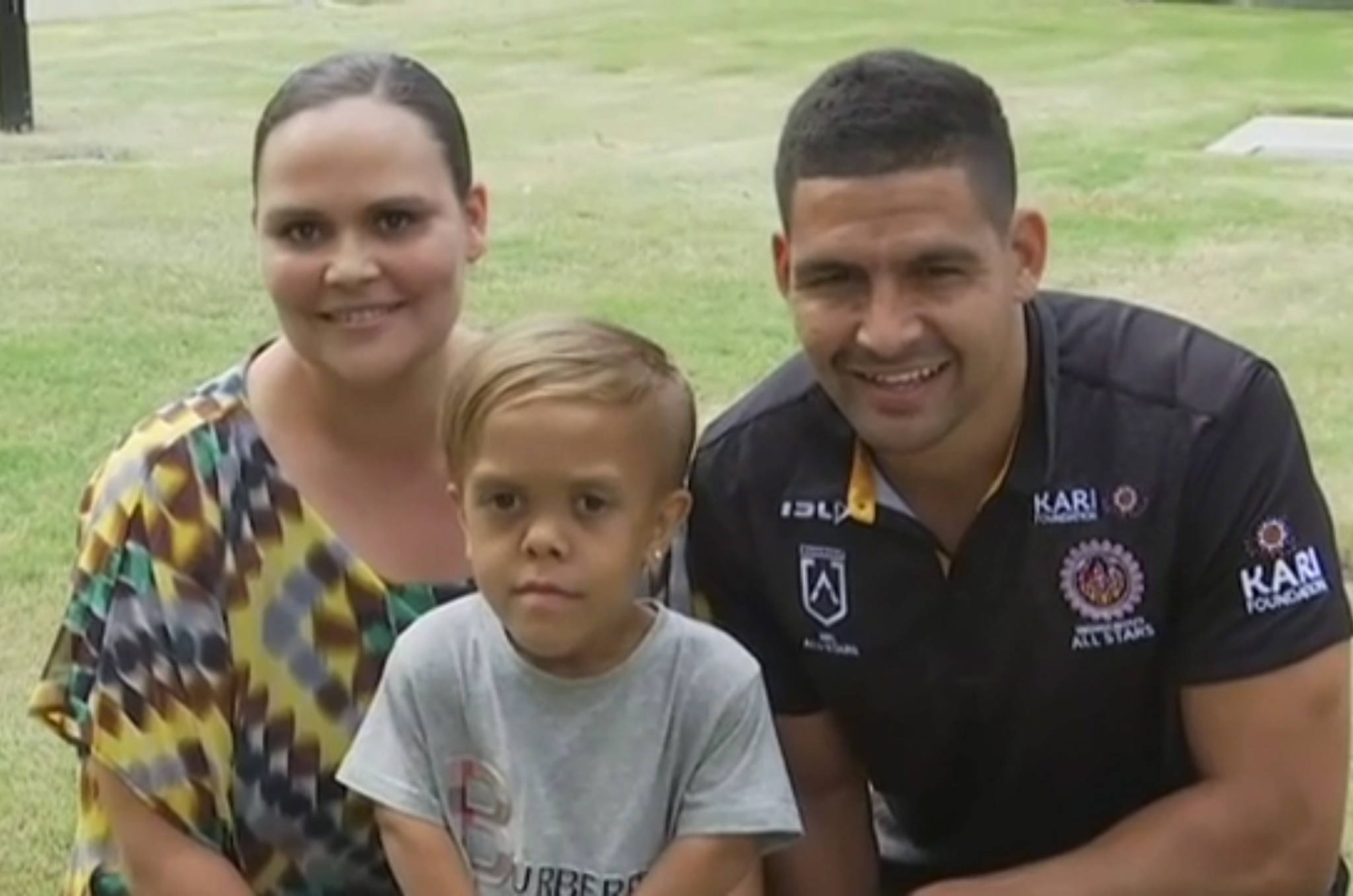 In this photo taken from video provided by Australian Broadcasting Corporation, Quaden Bayles, center, his mother, Yarraka Bayles, and Cody Walker, a professional rugby league player, pose together Friday, Feb. 21, 2020, in Gold Coast, Australia. Bayles, who has dwarfism, received an outpouring of support worldwide after his mother shared an emotional clip of him on social media. (Australian Broadcasting Corporation via AP)