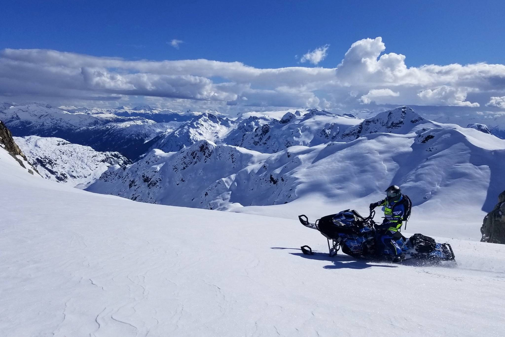 A snowmobiler enjoys the mountains in March 2019. Long, sunny days bring more people into the backcountry, but they can also impact the snowpack. Photo by Mike Conlan