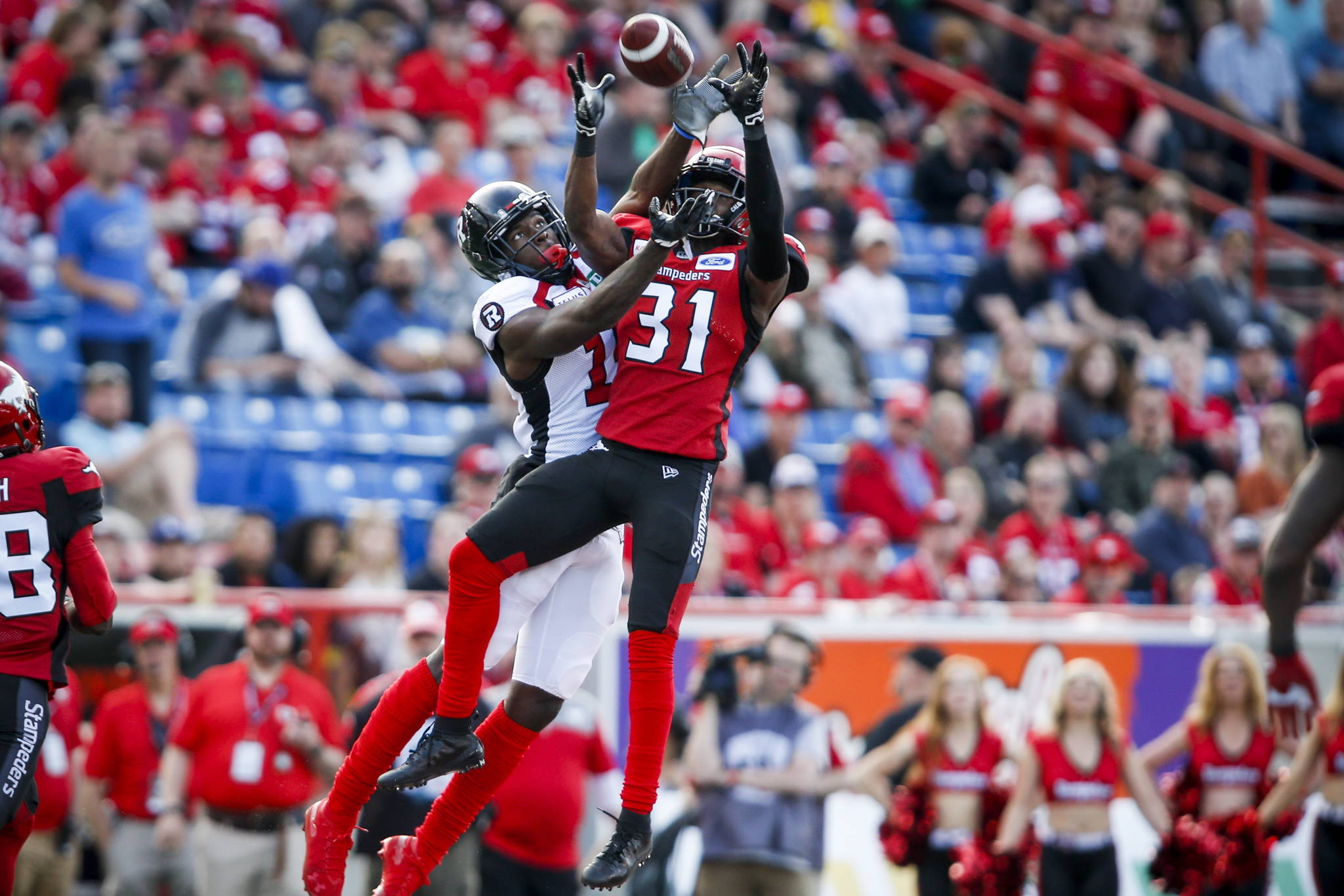 Ottawa Redblacks' Dominique Rhymes, left, looks on as Calgary Stampeders' Tre Roberson, catches a pass meant for him during first half CFL football action in Calgary, Saturday, June 15, 2019. The B.C. Lions have signed free-agent wide receiver Rhymes to a one-year contract.THE CANADIAN PRESS/Jeff McIntosh