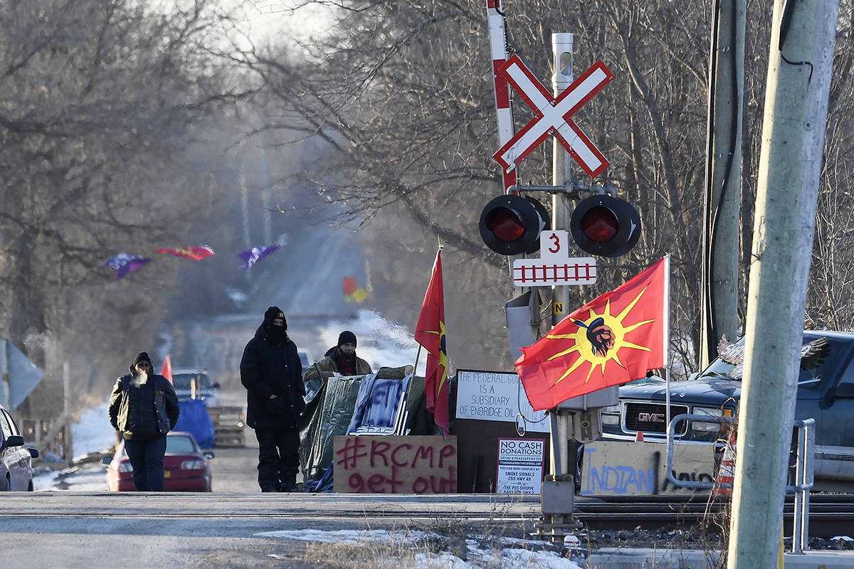 Protesters stand at a rail blockade in Tyendinaga Mohawk Territory, near Belleville, Ont., on Monday Feb. 24, 2020, during a protest in solidarity with Wet'suwet'en Nation hereditary chiefs attempting to halt construction of a natural gas pipeline on their traditional territories. THE CANADIAN PRESS/Adrian Wyld