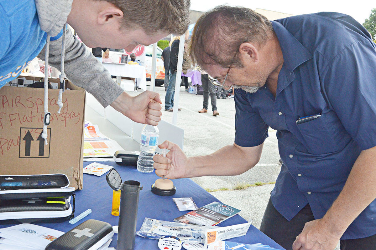 Norman Ayles, right, learned how to give a Naloxone injection to someone suffering from an opioid overdose, from Lookout Housing and Health Society staffer Levi Epp, left, at a 2019 overdose prevention event in Langley City. (Langley Advance Times files)